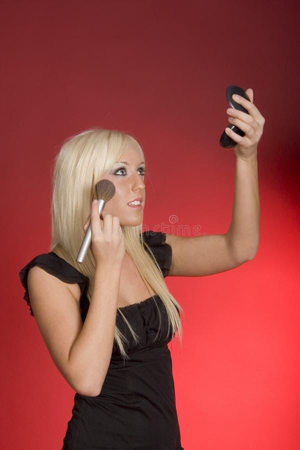 Supermodel. Blond teenage girl applying make-up royalty free stock photography