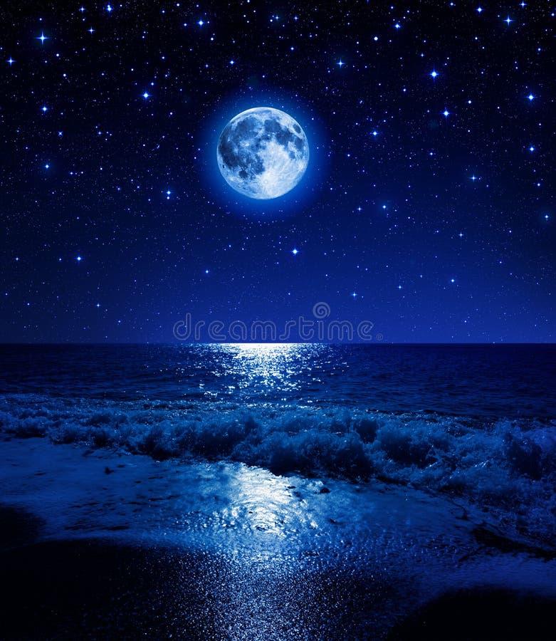 Supermond im sternenklaren Himmel auf Seestrand stockbild