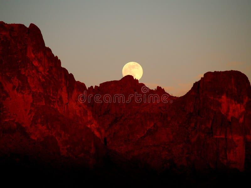 Supermoon поднимая над горами суеверия на заходе солнца стоковое изображение