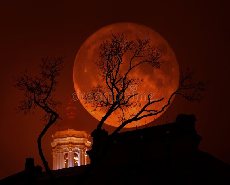 Supermoon rosso sangue con una chiesa e un albero in maltempo immagini stock