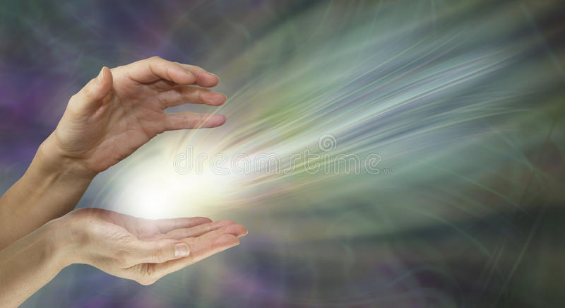 Supernatural electromagnetic energy field. Female healer's hands with a radiating white light energy formation between on a wide muted green and purple royalty free stock image