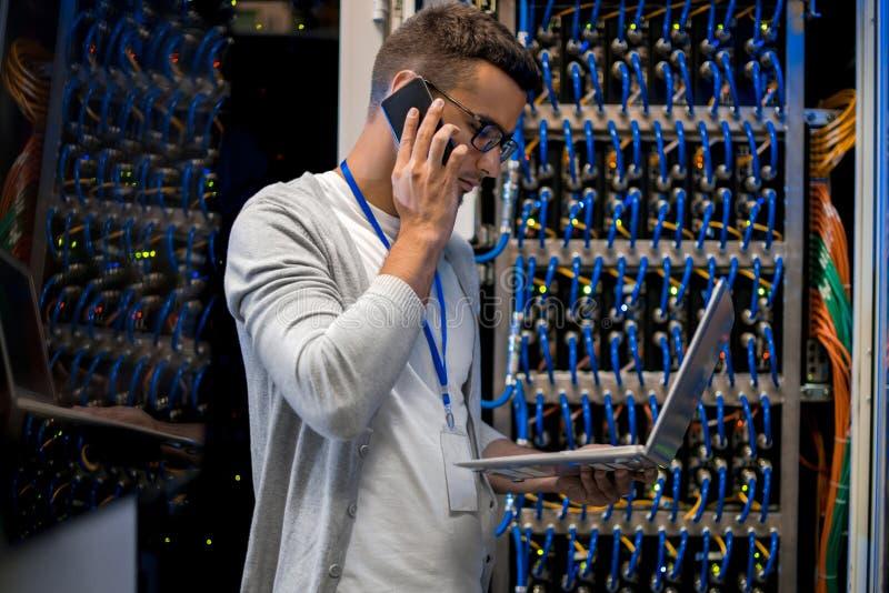 Superordenador de manejo del hombre vía el ordenador portátil fotos de archivo libres de regalías