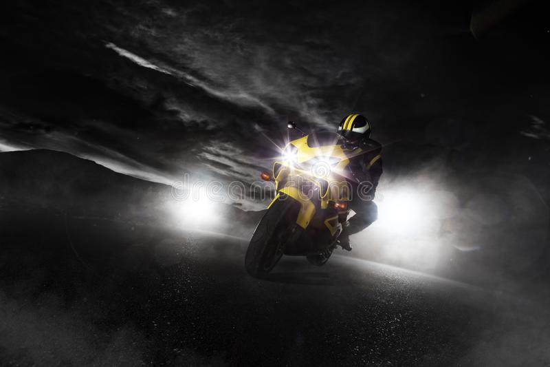 Supersport motorcycle driver at night with smoke around. Dark motorbike wallpaper stock images