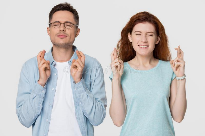 Superstitious young couple crossing fingers wishing for good luck concept stock photos