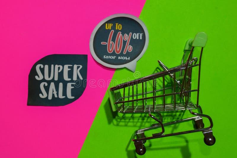 Superverkauf und bis -60% weg vom Geschäfts-jetzt Text und dem Einkaufswagen stockfotografie