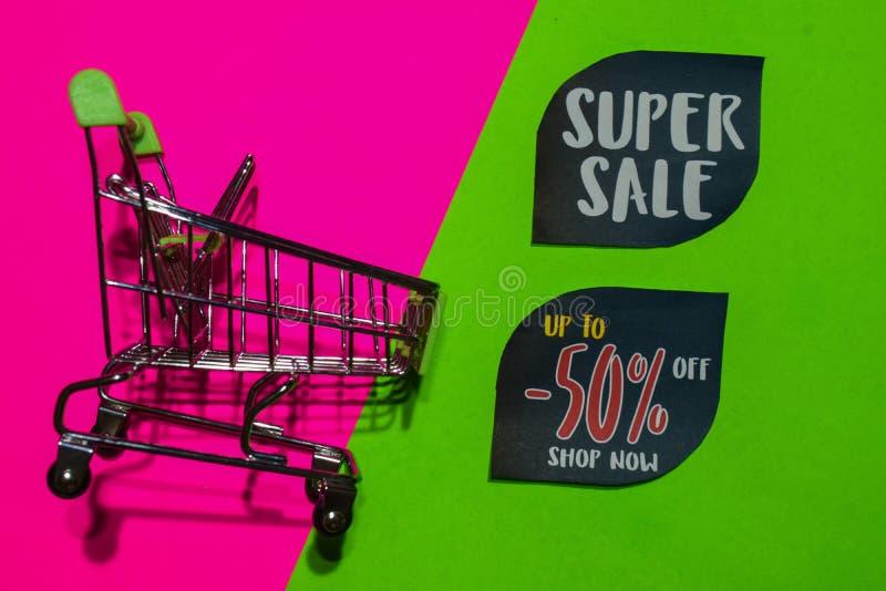 Superverkauf und bis 50% weg vom Geschäfts-jetzt Text und dem Einkaufswagen stockfotos