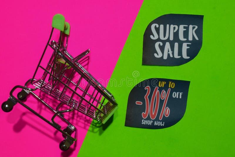 Superverkauf und bis -30% weg vom Geschäfts-jetzt Text und dem Einkaufswagen stockbild