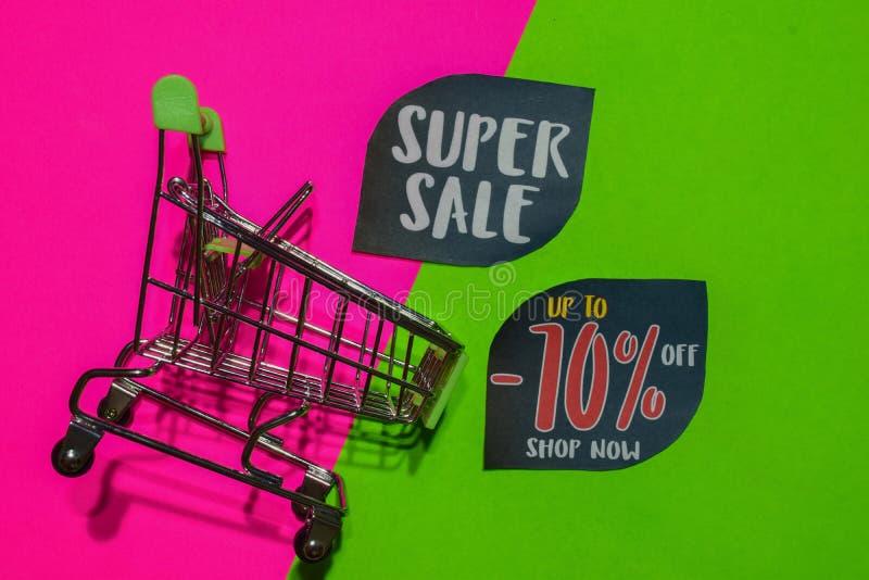 Superverkauf und bis -70% weg vom Geschäfts-jetzt Text und dem Einkaufswagen stockfotografie