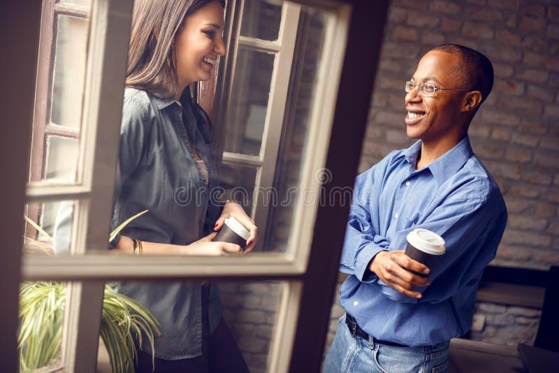 Supervisor afroamericano que habla con la mujer joven imagen de archivo