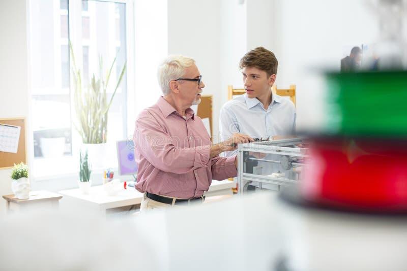 Supervisor agradável e interno que conversam ao medir o modelo 3D foto de stock