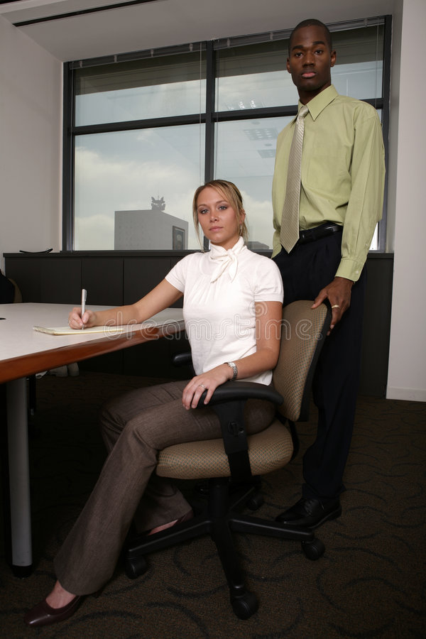 Supervisor behind associate taking notes royalty free stock images