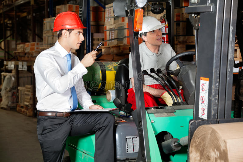 Supervisor With Clipboard Instructing Forklift. Male supervisor with clipboard instructing forklift driver at warehouse royalty free stock images