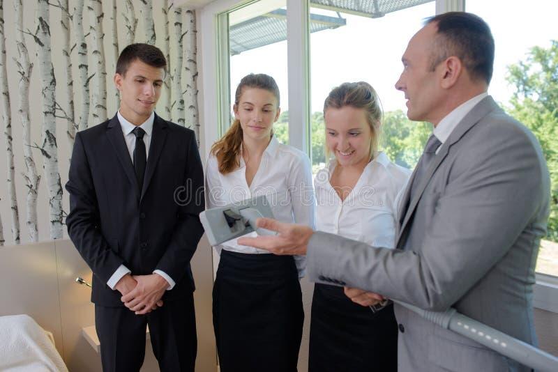 Supervisor die hotelpersoneel vacuümtapijtgehechtheid tonen royalty-vrije stock afbeelding