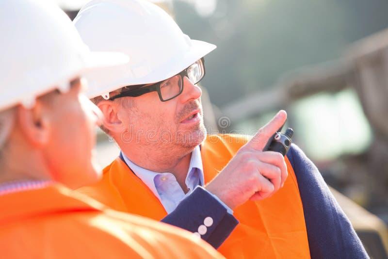 Supervisor die iets tonen aan collega bij bouwwerf royalty-vrije stock afbeeldingen