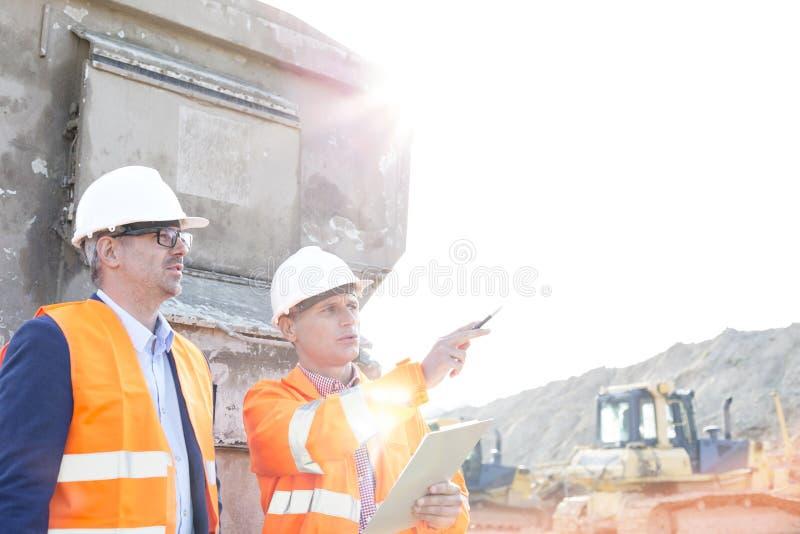 Supervisor die iets tonen aan collega bij bouwwerf op zonnige dag royalty-vrije stock afbeelding