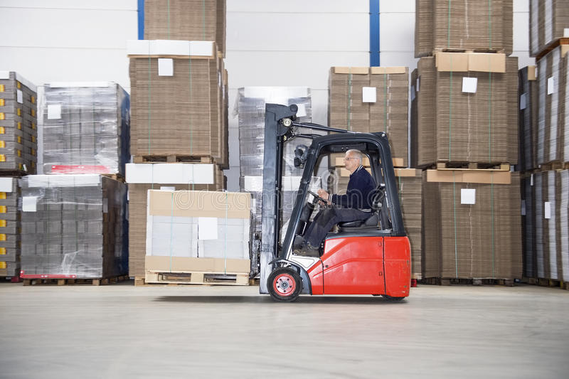 Supervisor Driving Forklift In Warehouse stock image