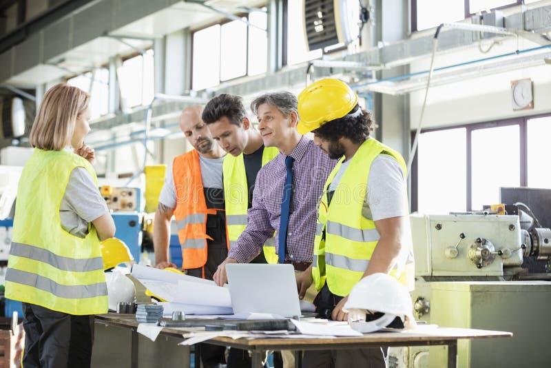 Supervisor en handarbeiders die over blauwdrukken in de industrie bespreken stock foto