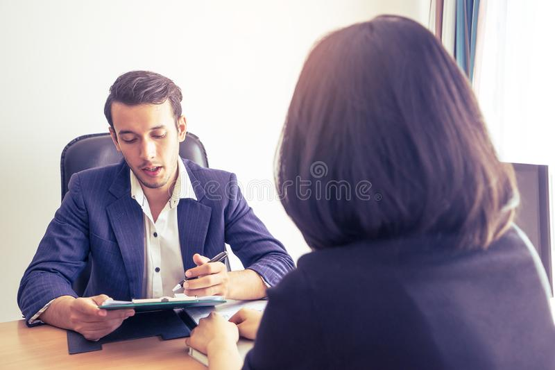 Supervisor explaining documents contractto a female worker stock photography