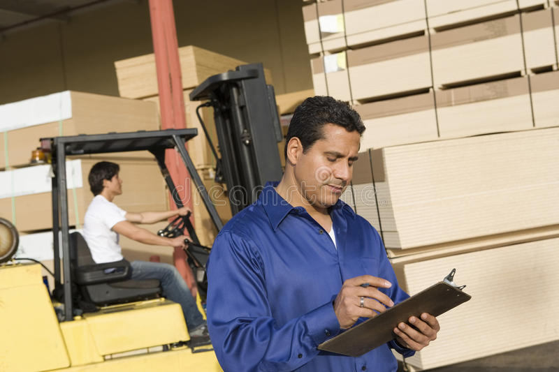 Supervisor And Forklift Truck Driver. Male supervisor with clipboard and forklift truck driver in the background royalty free stock image