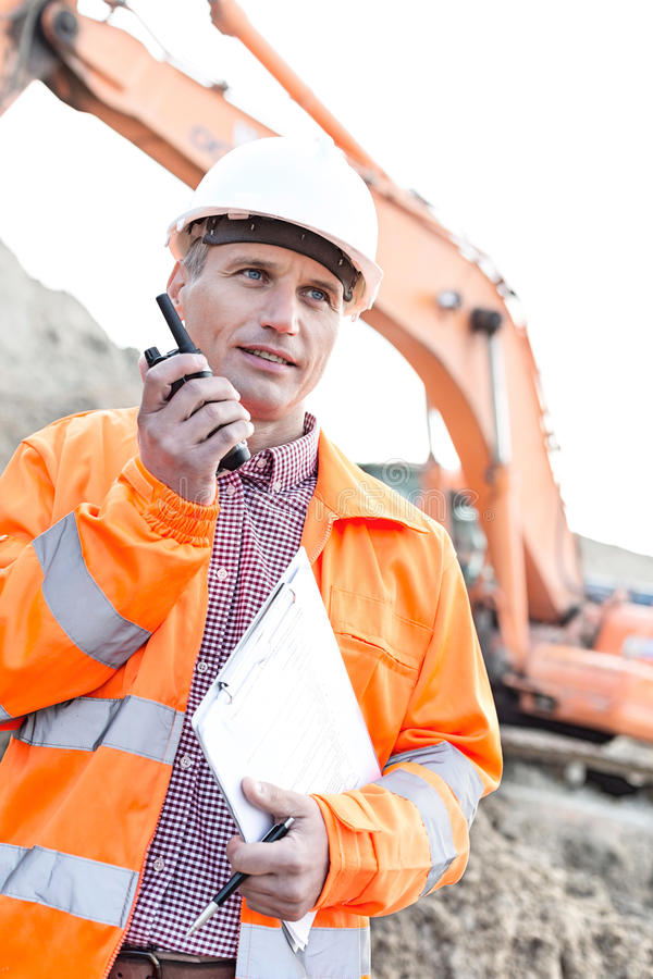 Supervisor holding clipboard while using walkie-talkie at construction site royalty free stock photography