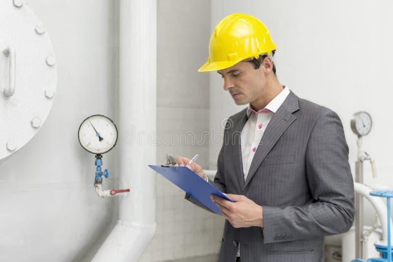 Supervisor masculino novo que inspeciona o encanamento na indústria fotografia de stock