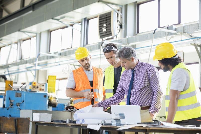 Supervisor met arbeiders die blauwdrukken onderzoeken bij lijst in de industrie stock fotografie