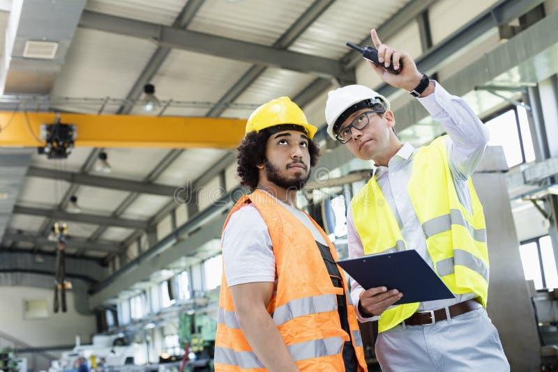 Supervisor que muestra algo al trabajador manual en industria de metal imagen de archivo