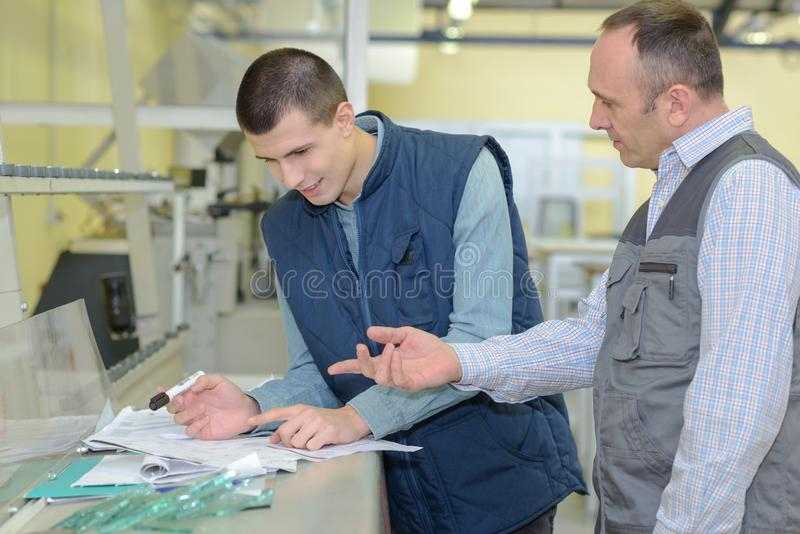 Supervisor questioning young worker stock photo