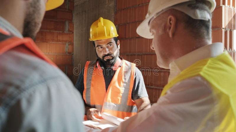 Supervisor Showing Building Plans To Workers In New House stock photos