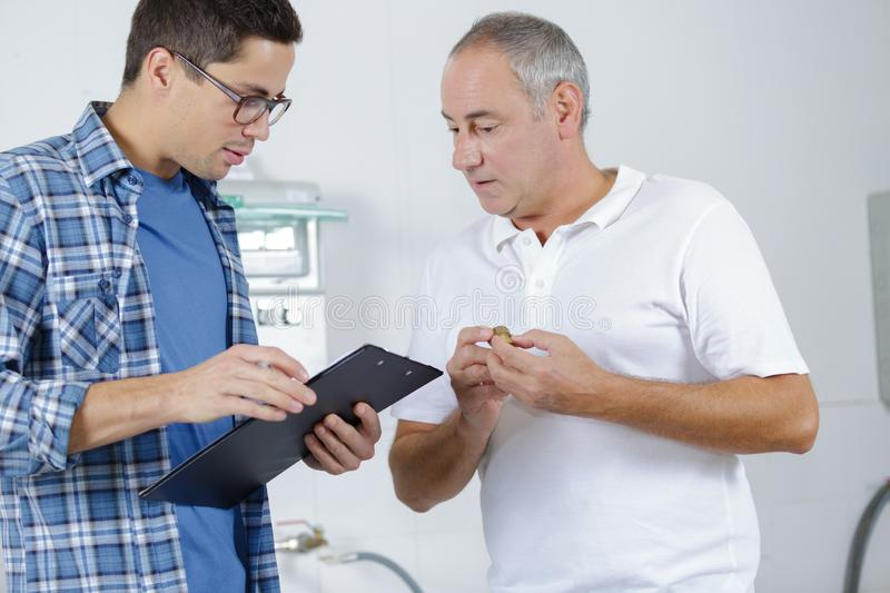 Supervisor showing clipboard to worker. Workers stock photo