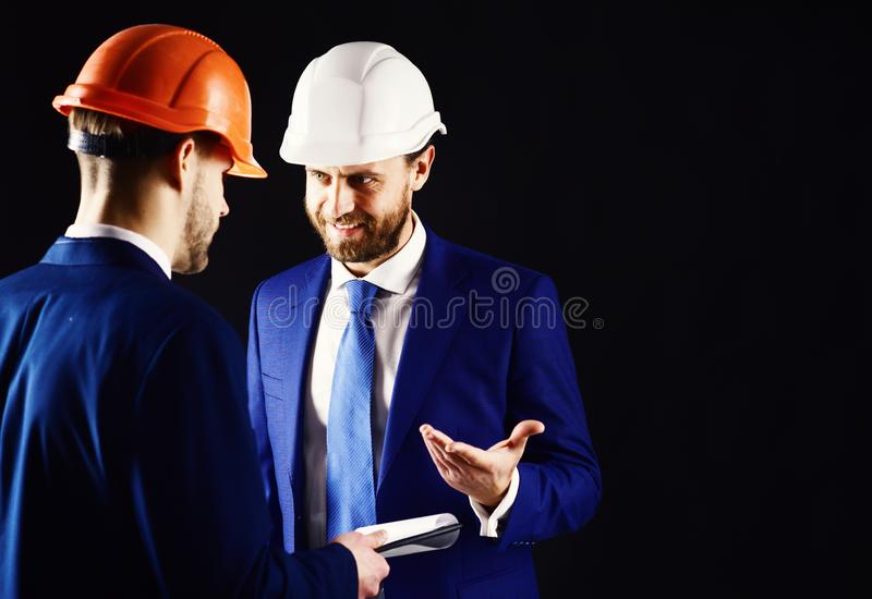 Supervisor and technician in helmets. Building inspector with smiling face talks to architect. Construction and happy royalty free stock photography