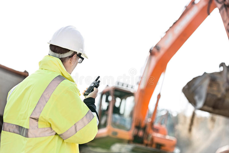 Supervisor using walkie-talkie at construction site against clear sky royalty free stock image