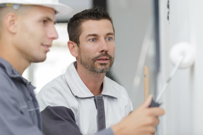 Supervisor watching apprentice painter use roller royalty free stock photos