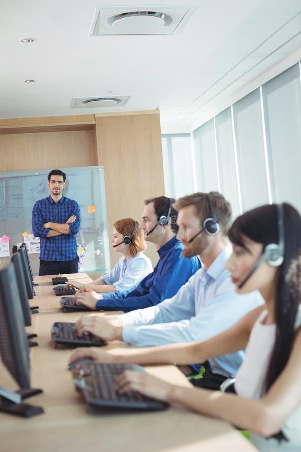 Supervisore con il gruppo di affari che lavora alla call center immagini stock libere da diritti