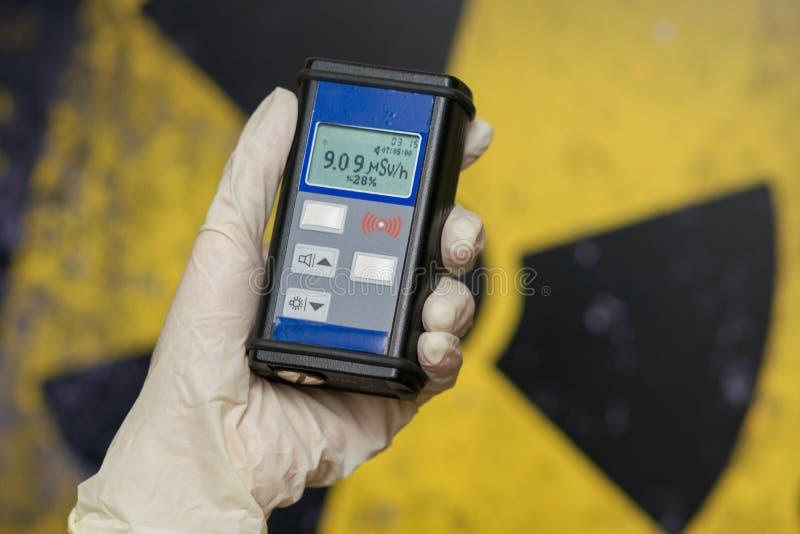supervisore di radiazione in vestiario di protezione e maschera antigas con i controlli di contatore Geiger il livello di radiazi immagine stock libera da diritti