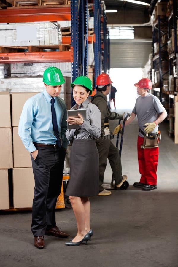 Supervisores com a tabuleta de Digitas que trabalha em imagem de stock