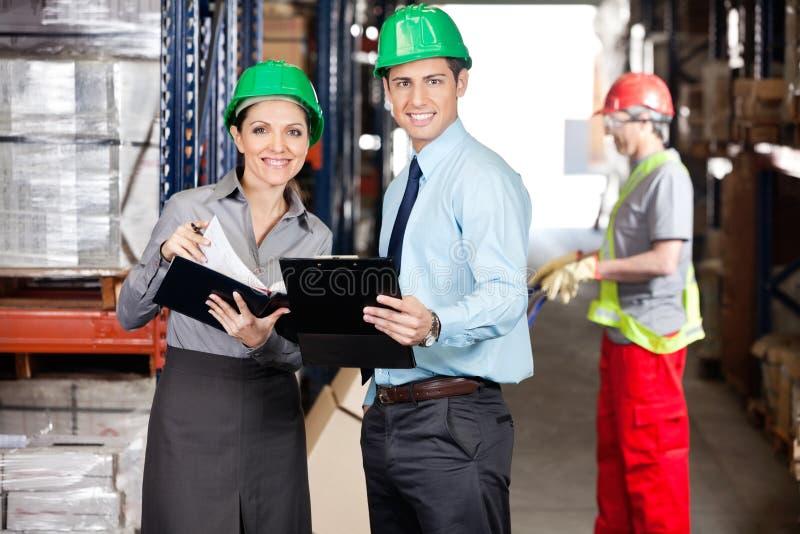 Supervisores que trabalham no armazém fotografia de stock