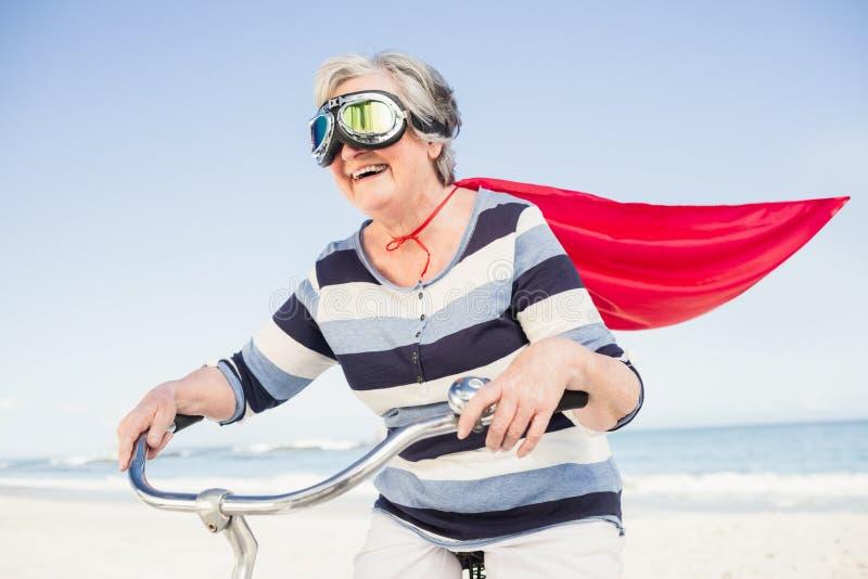 Superwoman supérieure sur un vélo photo libre de droits