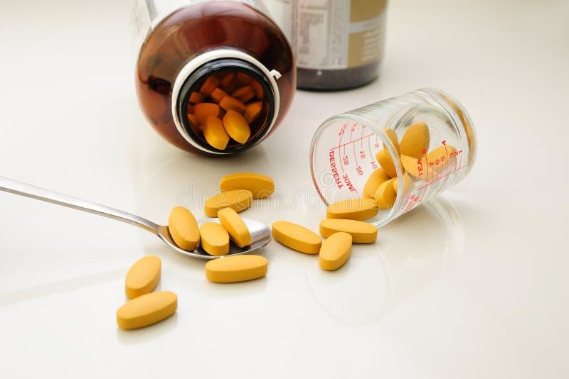 Suplemento alimenticio (píldoras) en cuchara y envases foto de archivo