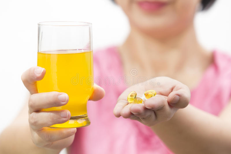Suplemento dietético a óleo e a colagênio de fígado de bacalhau no vidro para a bebida imagem de stock