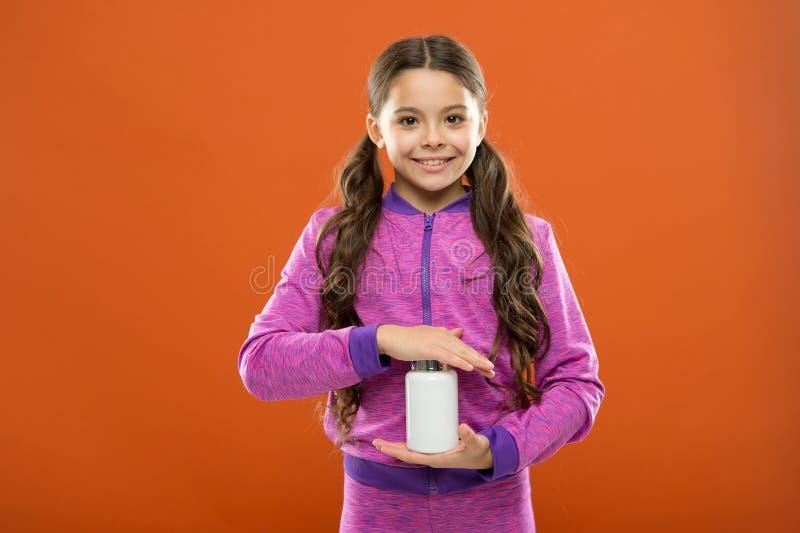 Suplemento dietético para crianças Suplementos à vitamina da tomada Garrafa das medicinas da posse da menina Conceito da vitamina foto de stock royalty free
