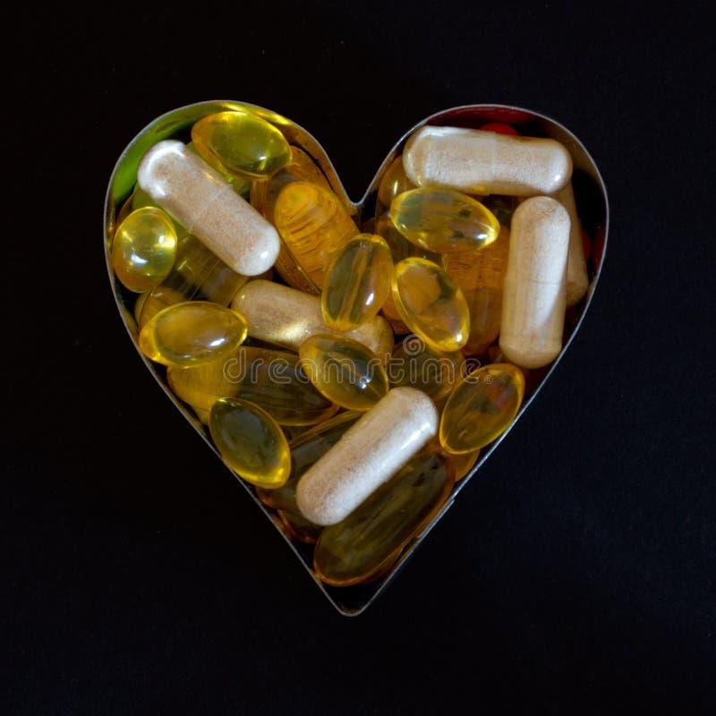 Suplementos dietéticos en cortador en forma de corazón de la galleta contra negro foto de archivo libre de regalías