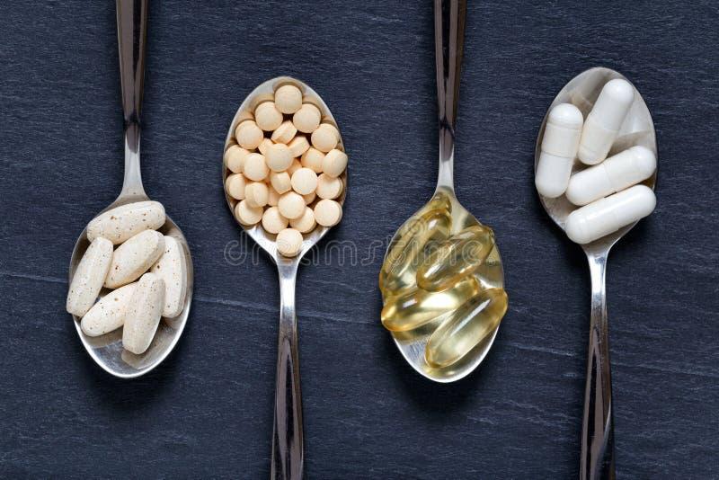 Suplementos sanos alternativos en las cucharillas foto de archivo libre de regalías