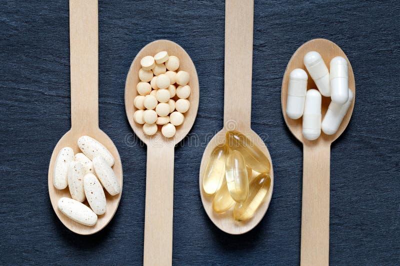 Suplementos saudáveis diferentes em colheres de madeira fotos de stock royalty free