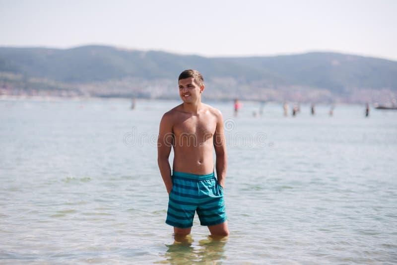 Suplente del hombre en el mar Varón hermoso en agua foto de archivo