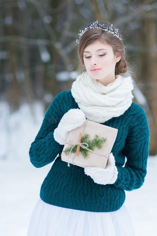 Supondo a jovem mulher que guarda o presente do Natal imagem de stock royalty free