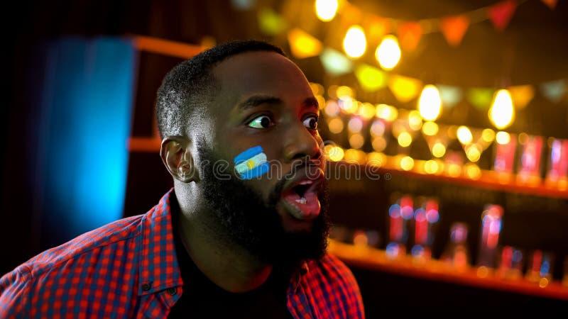 Suporte afro-americano com a bandeira argentina no mordente chocado com resultados fotos de stock royalty free