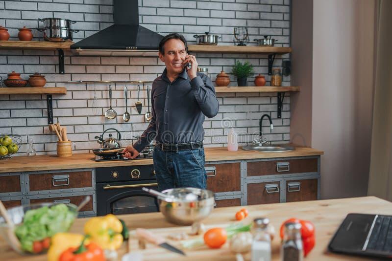 Suporte alegre do homem no fogão e conversa no telefone na cozinha Olha para trás e sorriso Portátil e vegetais coloful e fotografia de stock royalty free