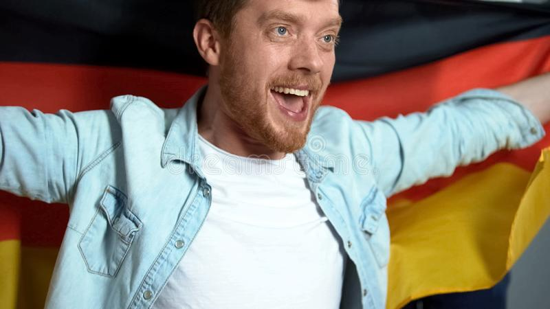 Suporte alemão que guarda a bandeira nacional, fósforo de futebol de observação, objetivo de júbilo imagem de stock royalty free