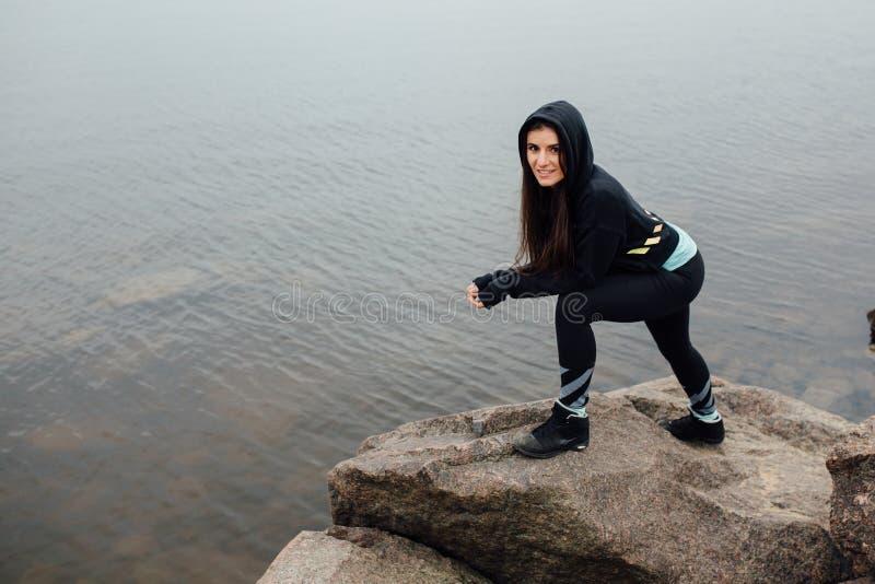 Suporte apto da mulher dos jovens em rochas e resto após um exercício duro imagens de stock